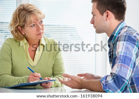 Teenager having a  therapy session while therapist is taking notes - stock photo