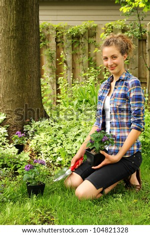 Teenager having purple flowers and tools to gardening