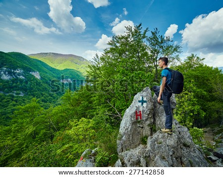 Teenager hiker boy with backpack on a peak in the mountains - stock photo