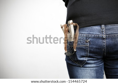 Teenager holding a wood slingshot in his back pocket - stock photo