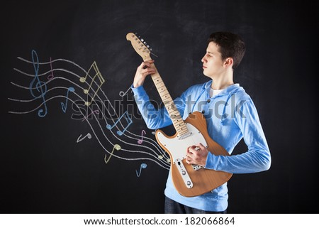 Teenager holding an electric guitar next to a blackboard - stock photo