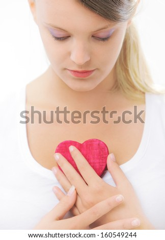 Teenager holding wooden heart in her hands