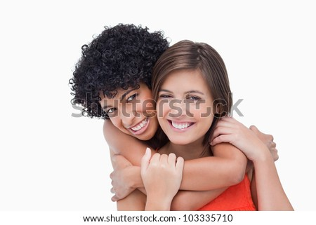 Teenager hugging her friend from the back - stock photo