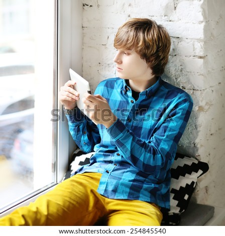 Teenager in blue shirt sitting on a windowsill at home and  taking pictures outside on the tablet - stock photo