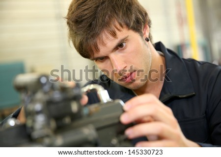 Teenager in professional training, repairing bike engine