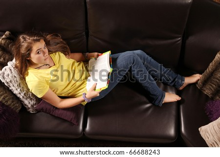 Teenager laying in a sofa and reading a book