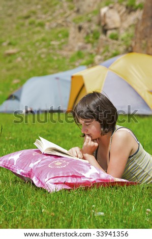 Teenager laying on grass reading a book - stock photo