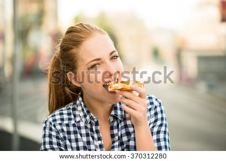 Teenager lifestyle - young woman eating pizza outdoor in street - stock photo