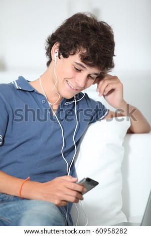 Teenager listening to music with mp3 player - stock photo