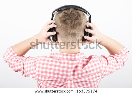 Teenager listens music with headphones on light background, rear view - stock photo