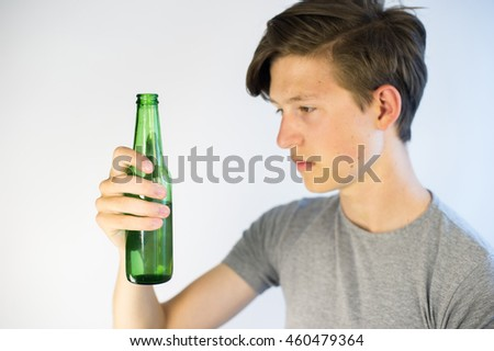 Teenager looking at a beer bottle with a sad expression.