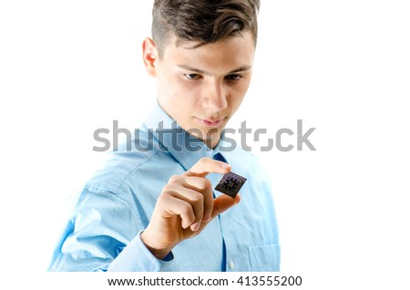 Teenager looking concentrated on a micro chip isolated on white background - stock photo