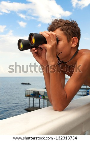 Teenager looks at the sea with binoculars. - stock photo