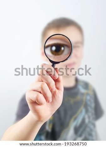Teenager looks through magnifying glass, big eye zoomed in - stock photo
