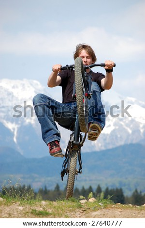 Teenager making tricks on a bicycle - stock photo