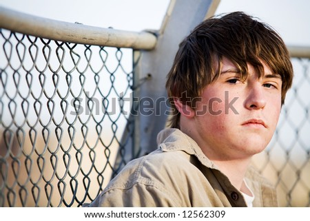 teenager male with natural look sitting against fence looking into camera