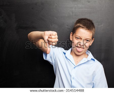 Teenager near blackboard showing dislike. Child at school. Student at classroom - stock photo