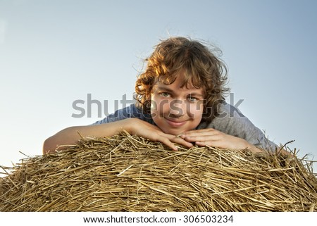 teenager on a haystack in the field in autumn - stock photo
