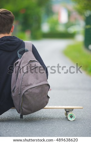 Teenager on a longboard casually sitting on his longboard on a suburban street.
