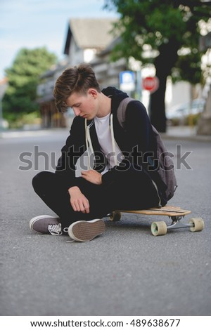 Teenager on longboard looking down.