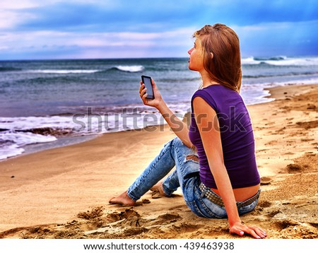 Teenager on sand near sea call help by phone. Summer girl sea back on water. Phone as means of communication with outside world.