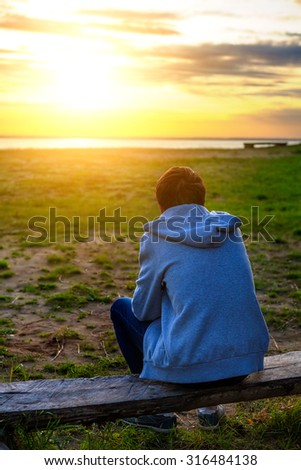 Teenager on the Nature at Sunset with the Sun in the Background