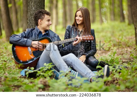 Teenager playing guitar for his girlfriend outdoor in the forest - stock photo