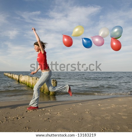 Teenager playing with ballons on the beach - stock photo