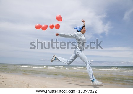 Teenager playing with red ballons on the beach - stock photo