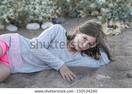 teenager playing with sand and wind - stock photo