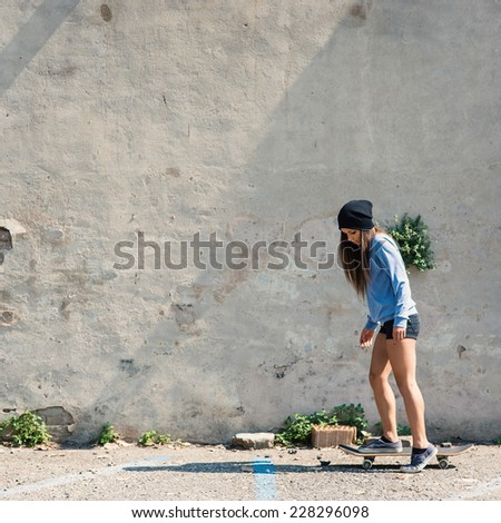 Teenager portrait riding skateboard against concrete wall.  - stock photo