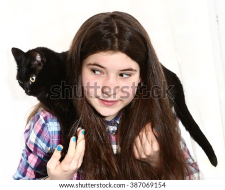 teenager pretty girl with long dark brown thick hairs hold black cat on shoulders close up portrait isolated on white - stock photo