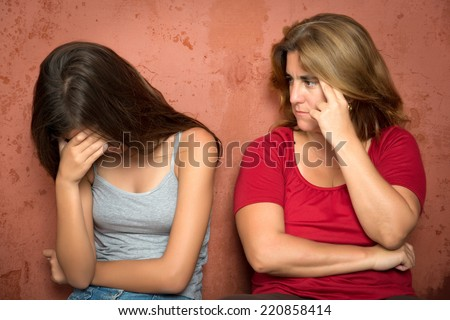 Teenager problems - Sad crying teenage girl and her worried mother - stock photo