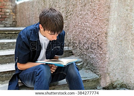 Teenager read the Book on the City Street - stock photo