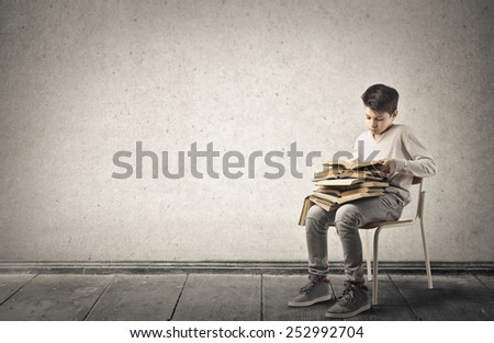 Teenager reading a pile of books  - stock photo
