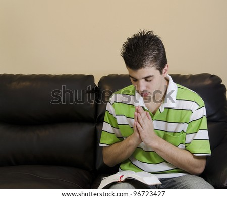 Teenager reading and praying in a Christian fashion to honor God - stock photo