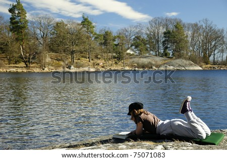 Teenager reading book in coast beautiful scenery - stock photo