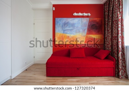 Teenager's room with a red wall and sofa - stock photo