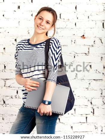 Teenager schoolgirl with textbook near the white brick wall