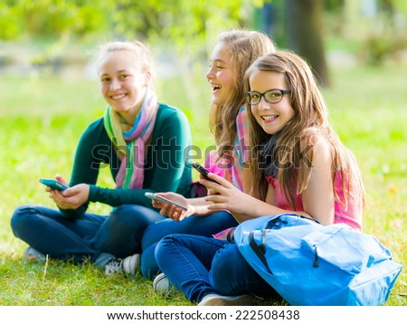 Teenager schoolgirls having fun with mobile phones in the park - stock photo