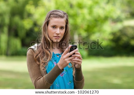 Teenager sending a text while standing in a park and looking at the camera - stock photo