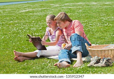 Teenager siblings reading book at picnic in the park in a bright sunny day