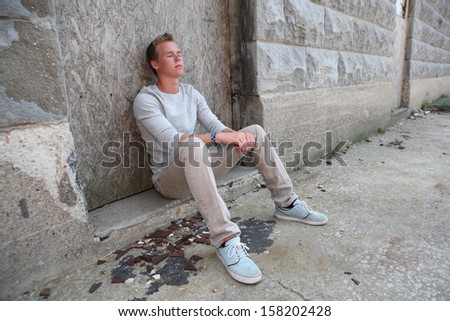 Teenager sitting in an alley with eyes closed