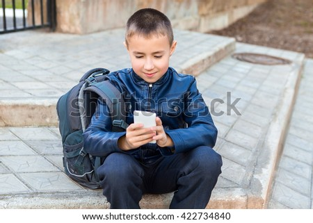 Teenager sitting in the Park and watching with a phone and a backpack - stock photo