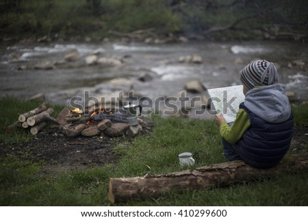 Teenager sitting near a fire in camping and watching map. - stock photo