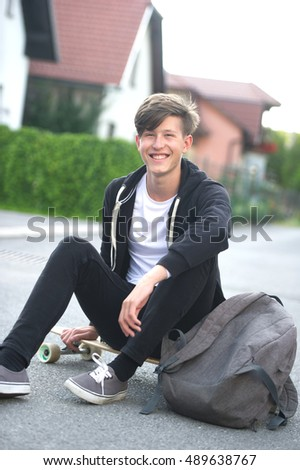 Teenager sitting on his board with his backpack near him and smiling.