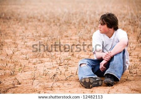 teenager sitting outdoors in wilderness area, dry lake bed among the weeds