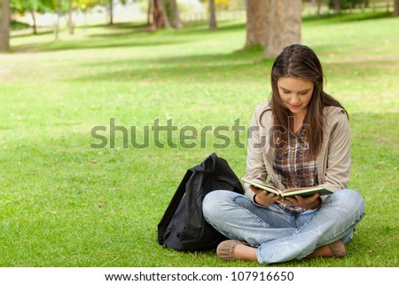 Teenager sitting while reading her textbook in a park - stock photo