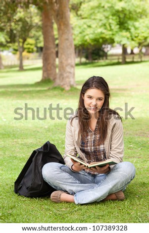 Teenager sitting with a textbook in a park while looking at camera - stock photo