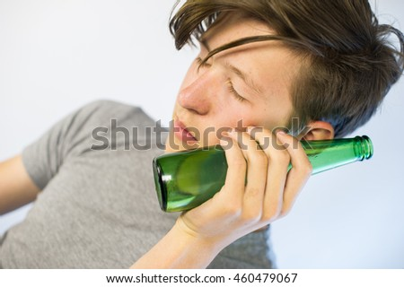 Teenager sleeping on a beer bottle.